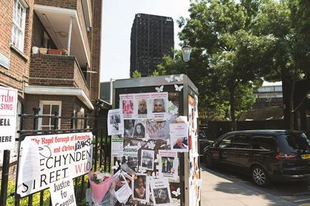 Floral tributes and missing person posters  left on a street corner in the London Borough of Kensington and Chelsea after the Grenfell Tower fire